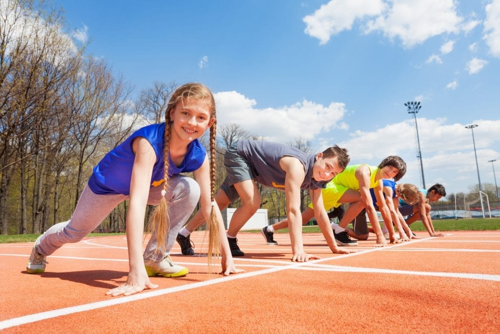Side view of five teenage sprinters in sportswear lined up ready to race at the stadium