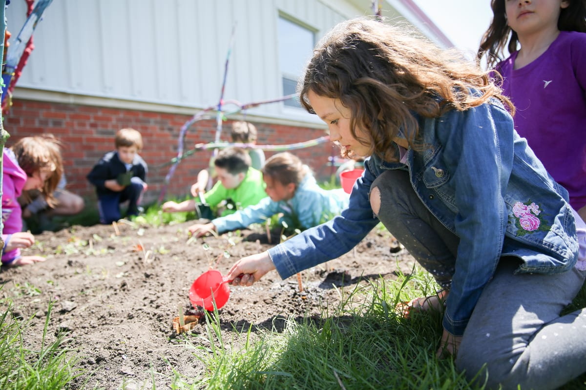 A student waters a garden bed during a nature play workshop.