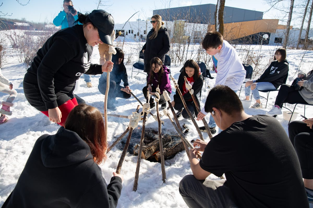 Students cook bannock over an open fire at a Traditional Foods Camp in Enoch, Alberta.