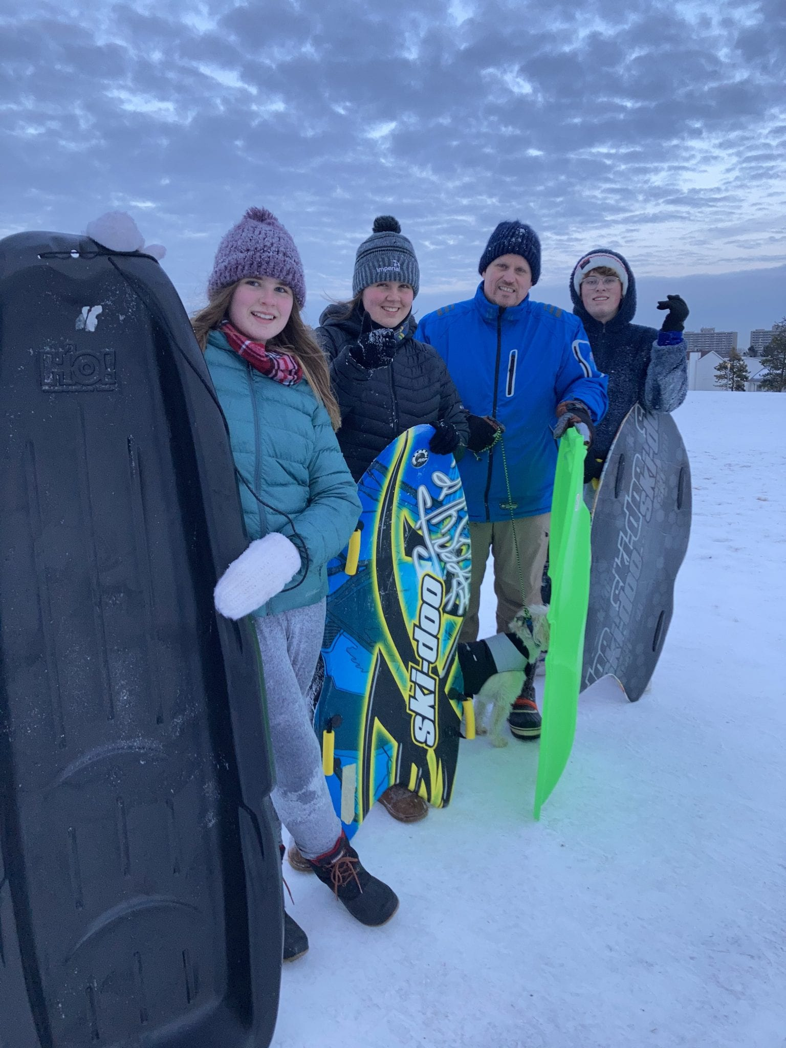 Four people outside wearing winter gear hold sleds and smile for the camera for Family Day.