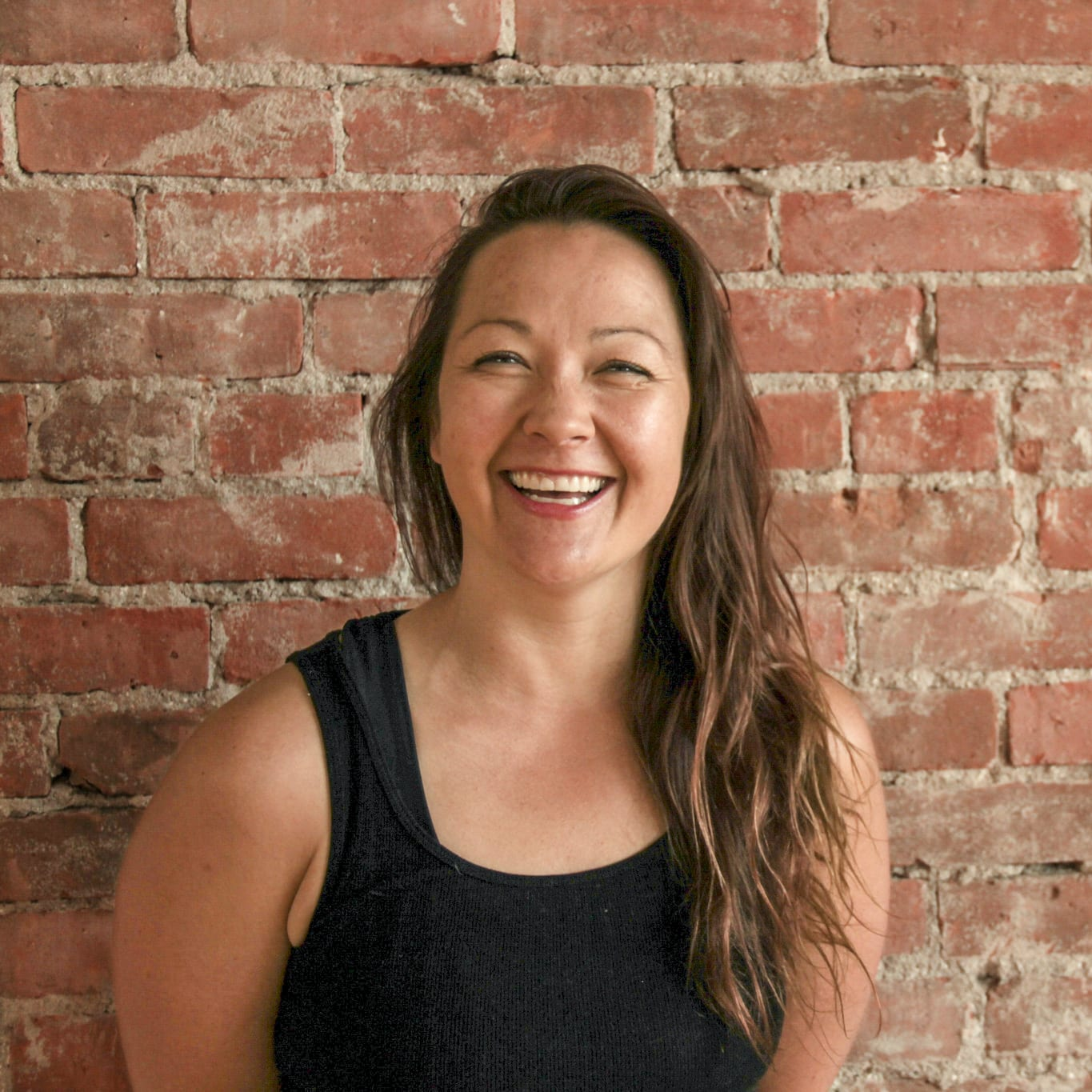 Shonna Lamb, wearing a black tank top, with long wavy brown hair, smiles while standing against a red brick wall.