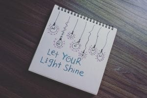 """A drawing of black lightbulbs with purple flashes, and blue text below: """"Let Your Light Shine"""""""