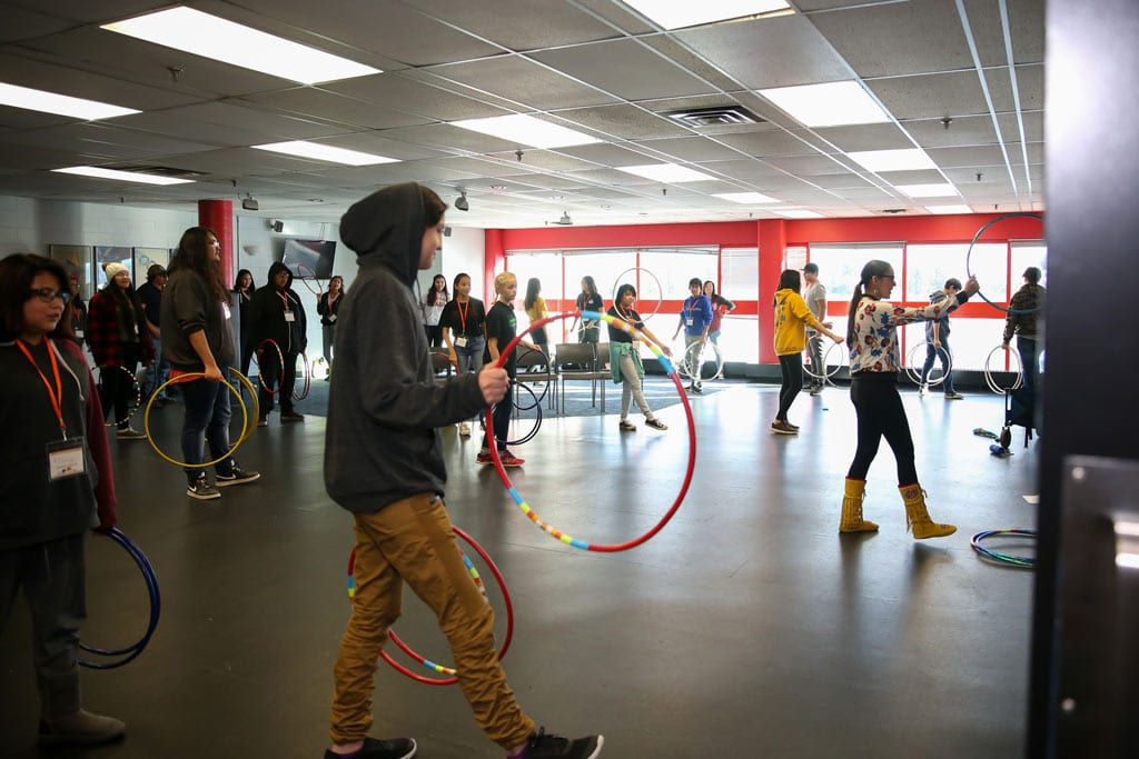 Sandra Lamouche teaches a hoop dance class to a group of youth. Sandra is seen on the right side of the image holding a hoop at eye level while the youth are seen filling the room copying her.