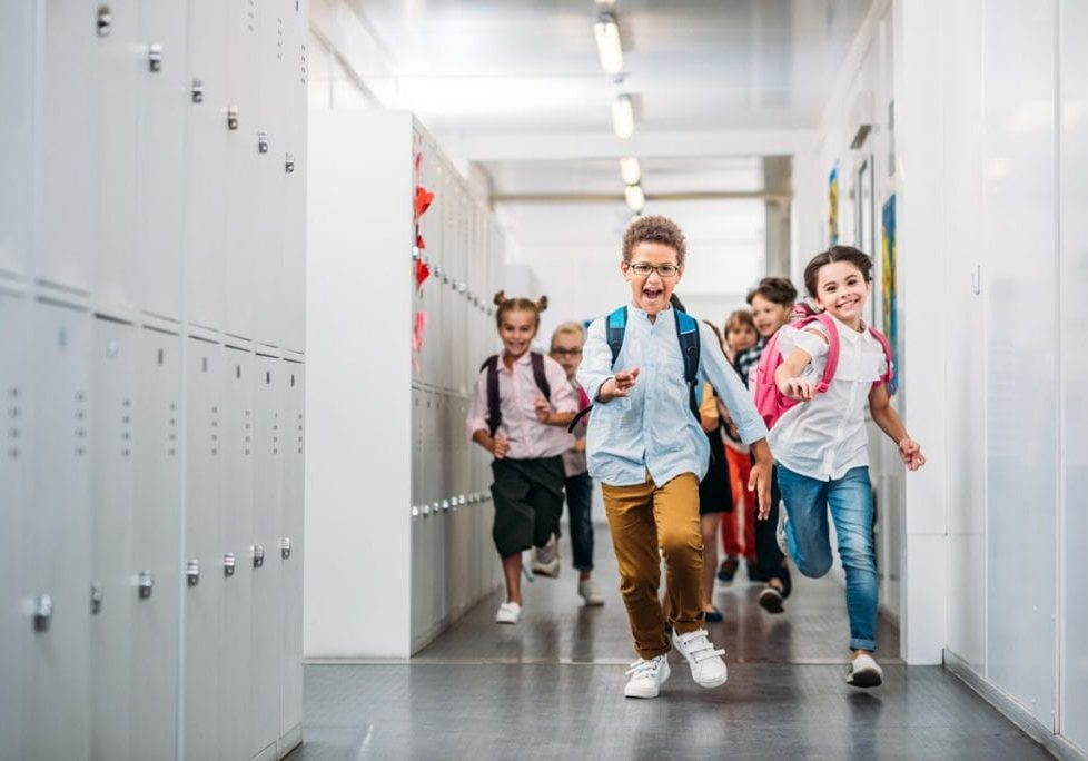 cute funny pupils running through school corridor
