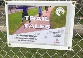 "A laminated, corrugated plastic board with an image on it that says ""Trail Tales"". This is the introductory page to inform passersby of the purpose of the Trail Tales project."