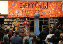 Indigenous people make a presentation to a crowd in a school library