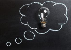 A blackboard with a lightbulb placed on it and a chalk drawing of a thought bubble around the bulb to indicate a thought or idea.